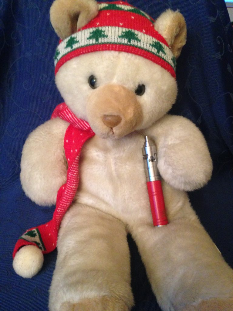 Un nounours blanc avec écharpe et bonnet rouge vapotant une e-cigarette rouge