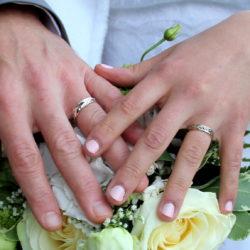 Mains avec alliances sur bouquet de mariage