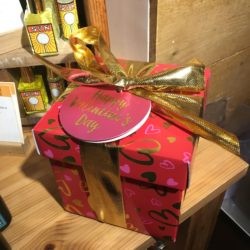 Jolie boîte rouge à petits coeurs roses et dorés, entourée d'un ruban doré