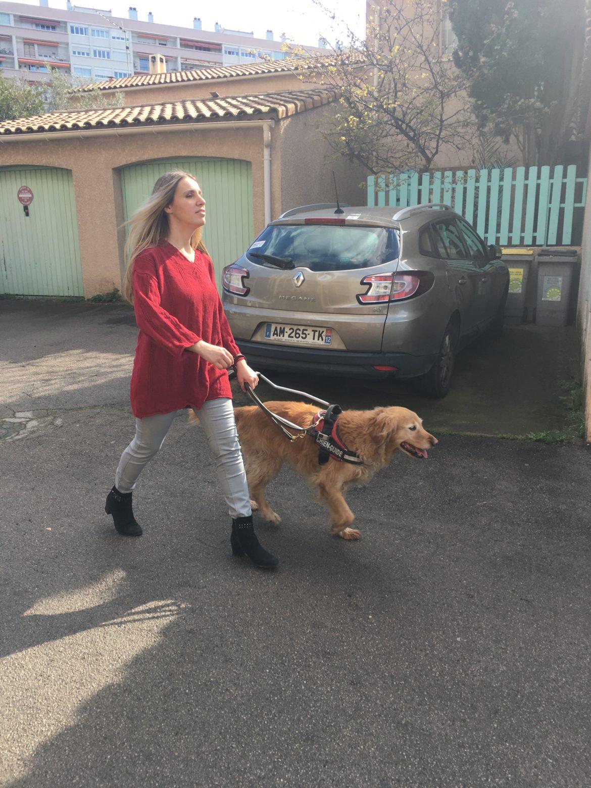 Florie marche avec Elba au harnais dans la rue