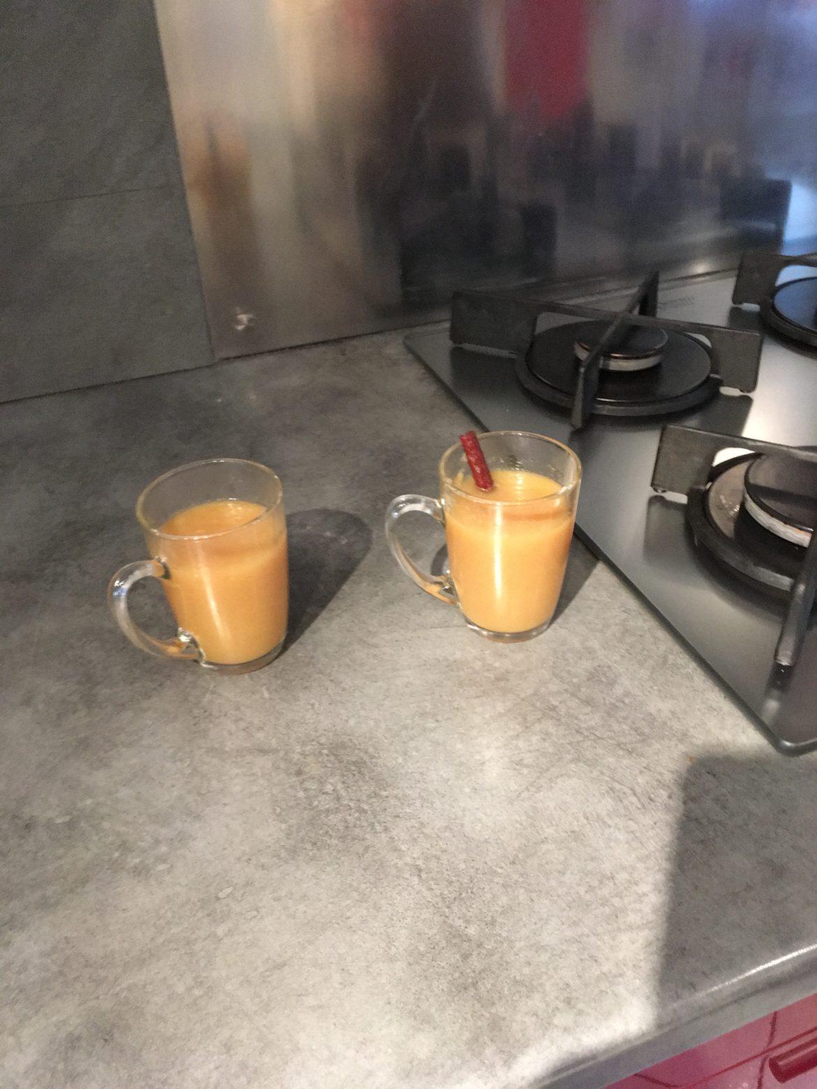Deux tasses transparentes contenant un jus de pommes trouble et un bâton de cannelle