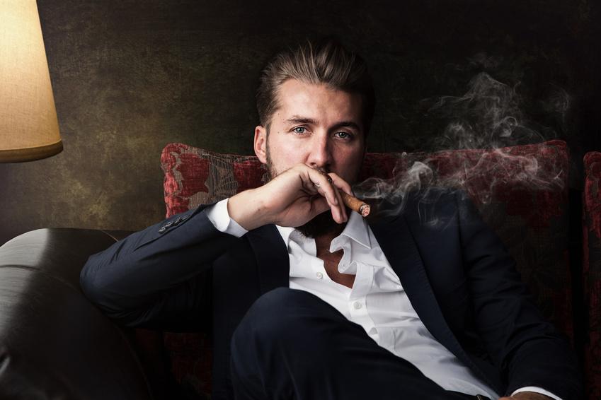Un homme fumant un cigare dans un nuage de fumée