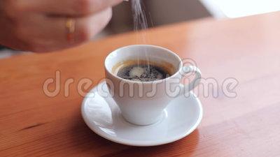 Main versant du sucre blanc dans une tasse
