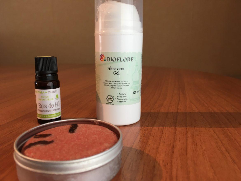 Un shampoing solide et des flacons posés sur une table en bois
