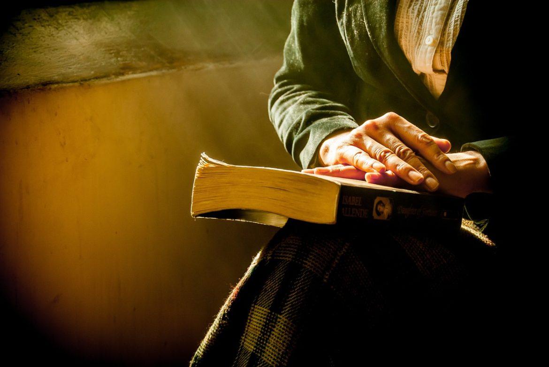 Femme avec mains sur un livre
