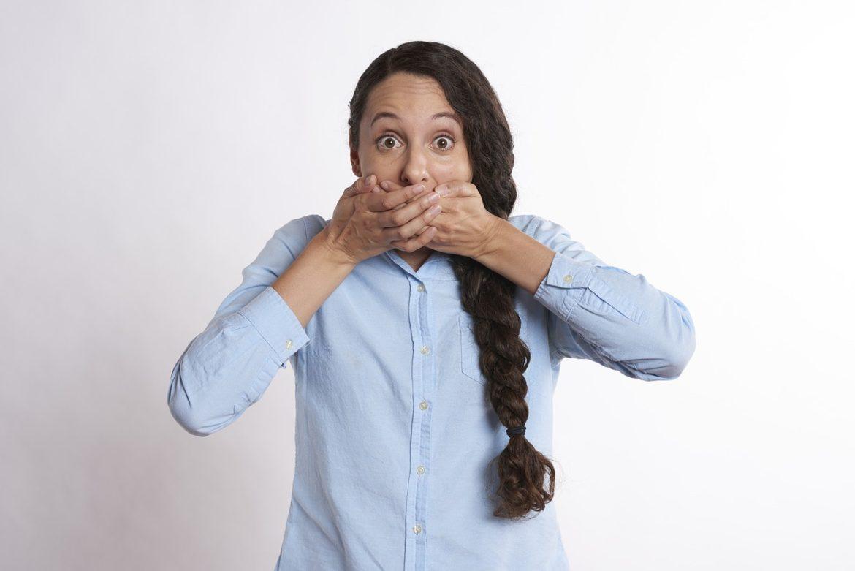 Femme avec une main sur la bouche