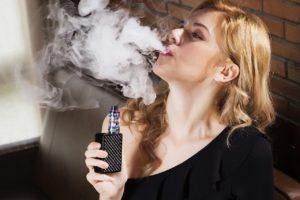 Femme tenant une cigarette électronique