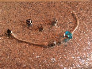 Bracelet d'argent ouvert avec plusieurs perles dans les tons bleus, certaines dessus, d'autres à côté