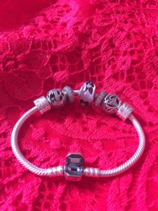 Bracelet en argent avec une perle de verre mauve contenant de petits papillons et deux perles d'argent représentant un F et un B ouvragés
