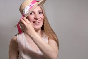 Flo très souriante portant un grand chapeau de paille qu'elle tient d'une main