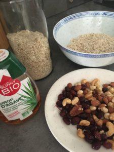 Sur un plan de travail, des fruits secs dans une assiette, des flocons d'avoine dans un bol et un flacon de sirop d'agave