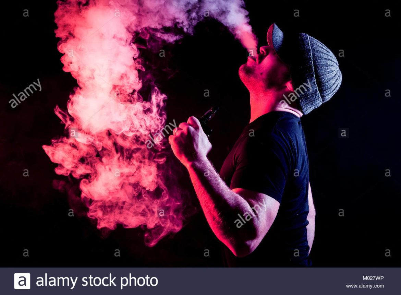 Un homme tenant un mod sur fond noir faisant un gros nuage de vapeur