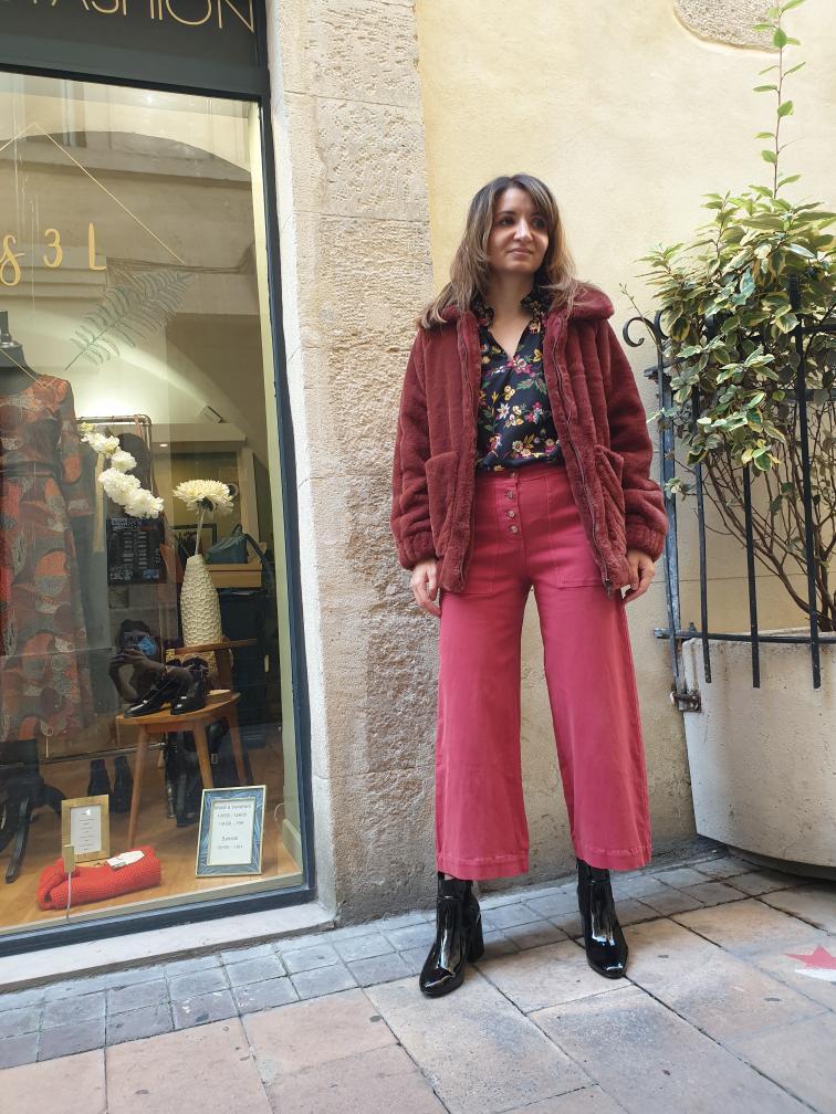 Ana, debout, en pied, bras le long du corps dans un ensemble bordeaux, devant la vitrine de la boutique Les 3 L. Elle tourne légèrement la tête et regarde vers la droite avec une expression sérieuse.