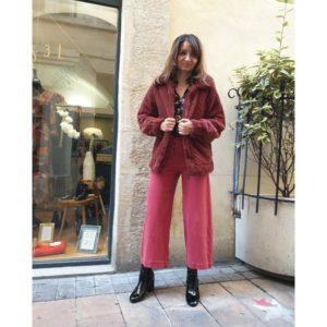 Devant un mur en pierres, en extérieur, Ana debout en pied dans un ensemble, pantalon et blouse, dans les tons bordeaux. Elle porte des bottines et un manteau dont elle tient les pans