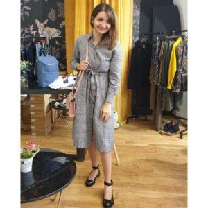 Ana, debout et vue en pied, porte une robe grise à carreaux très chic, des chaussures vernies et un petit sac à main rose sur l'épaule dont elle tient la lanière. Elle affiche un petit sourire.