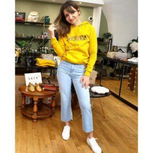Ana est debout, en pied, vêtue d'un sweat jaune à capuche, d'un jean et de baskets blanches. Elle sourit et tire sur une de ses mèches de cheveux