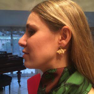 Boucles d'oreilles portée par Flo, en forme d'éventail dans les tons dorés (vue de plus loin)