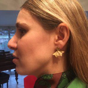 Boucles d'oreilles portée par Flo, en forme d'éventail dans les tons dorés (prise de près)