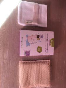 2 gants à savon, un avec son sur-gant, à côté de la boîte