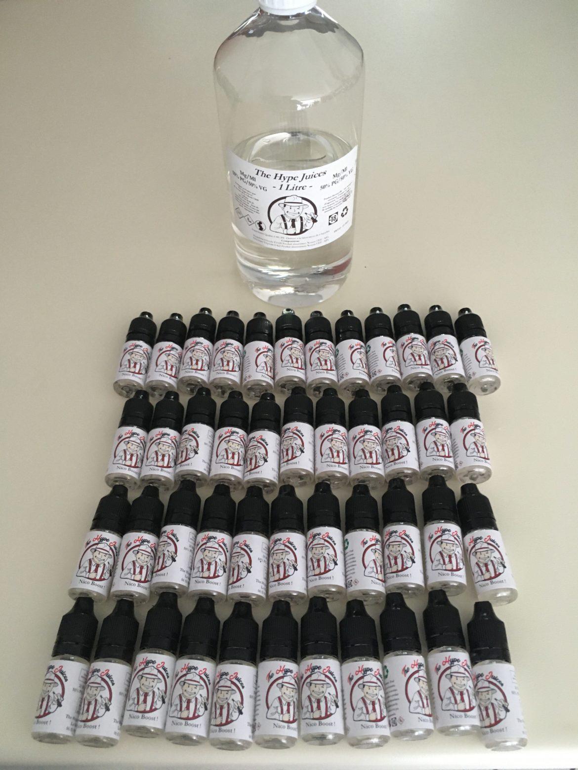 Un grand flacon de base pour e-liquides entouré d'une quantité impressionnante de petits flacons de boosters nicotinés