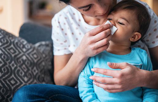 Maman aidant son bébé à moucher son nez