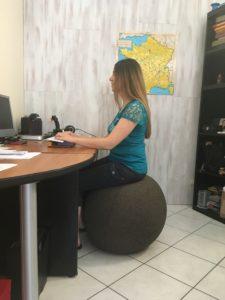 Flo de profil assise bien droite sur un gros ballon brun devant un bureau